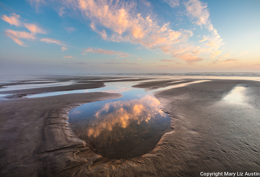 Tillamook County, Oregon: Colorful sunset sky reflected in tide pools at low tide