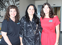 NWA Democrat-Gazette/CARIN SCHOPPMEYER Sherry Stephens (from left), Viviana Pagan and Shawnda Schnurbusch, Dress for Success NWA board president, welcome volunteers and partners to an appreciation reception June 18 at Crossland Construction in Rogers.