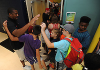 NWA Democrat-Gazette/ANDY SHUPE<br /> Scotty Thurman (left), director of student-athlete development for the University of Arkansas men's basketball team, greets students Wednesday, July 29, 2015, as they wait in line to receive school supplies and backpacks at the Boys and Girls Club of Fayetteville. The backpacks were filled with school supplies as needed, all provided by Dwelling Place Church, the Upsilon Chapter of Omega Psi Phi, the Gamma Eta Chapter of Omega Psi Phi, the Boys and Girls Club of Fayetteville, Walgreens, the University of Arkansas men's basketball team, and the Ronnie Brewer Foundation. After receiving a backpack and school supplies, the students spent time with the student-athletes and Brewer.