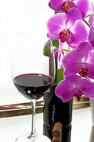 A relaxing glass of red wine combined with the bottle and orchids on a mirror surface