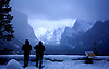 TWO TOURISTS ENJOY THE CLOUDS AND FOG ROLLING IN AND OUT OF YOSEMITE VALLEY DURING A SNOWSTORM IN YOSEMITE NATIONAL PARK, CALIFORNIA