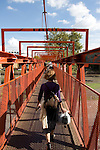 Buenos Aires, Argentina - An Argentine women walks across a pedestrian bridge  over train tracks in Buenos Aires