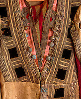 A detail of the front of a heavily decorated robe, its edging now frayed and the pink silk faded
