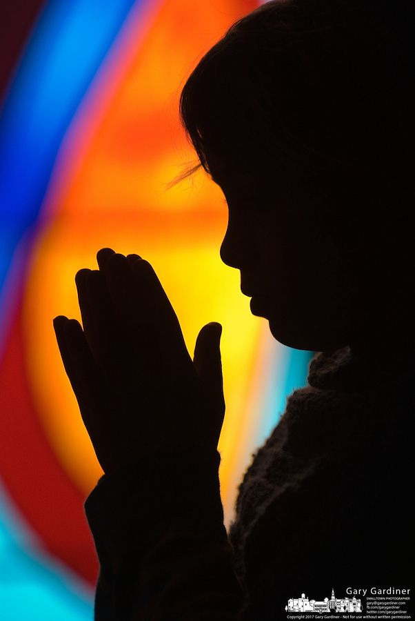 A young girl's hands are raised up in supplication during prayer at Mass at a Catholic church in Columbus, Ohio<br />