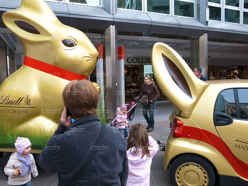 Switzerland. Canton Ticino. Lugano. Just before Easter, a marketing campaign  for Lindt chocolate. A golden rabbit and a Smart car in downtoan Lugano. Mother and children. 02.04.10  © 2010 Didier Ruef