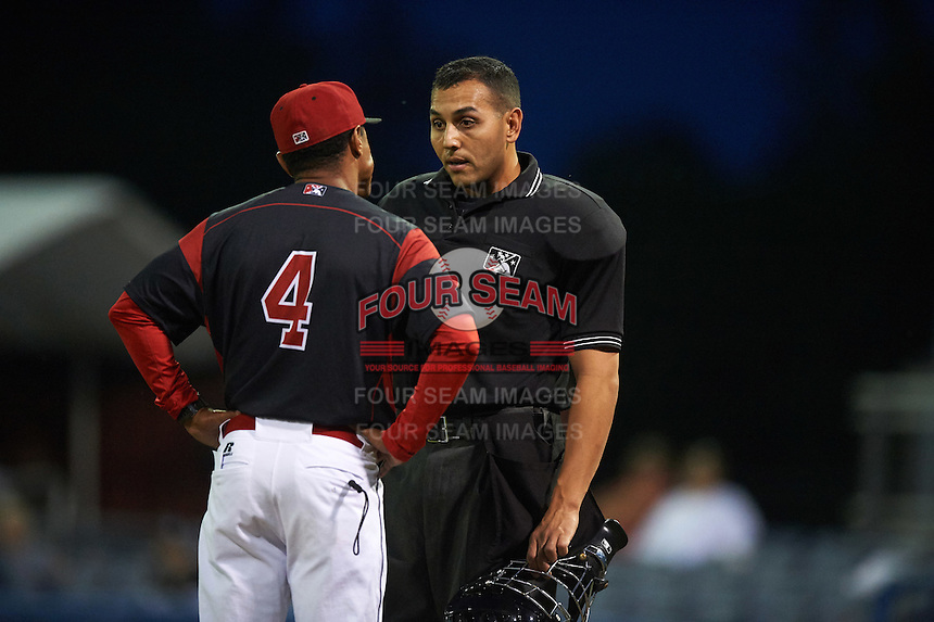 Batavia Muckdogs manager Angel Espada (4) talks with umpire Raul Moreno during a game against the West Virginia Black Bears on August 20, 2016 at Dwyer Stadium in Batavia, New York.  Batavia defeated West Virginia 7-2. (Mike Janes/Four Seam Images)