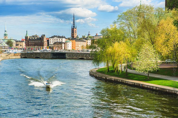 Liten motorbåt kör snabbt i Klarabergskanalen med vårutslagna tröd i Stockholm