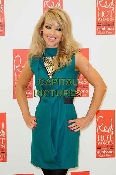 KATIE PIPER .attends Red magazine's 'Red Hot Women Awards' at the Saatchi Gallery, London, England, UK, .November 30th 2010..half length hands on hips green teal dress necklace smiling burns victim acid face scar burned gold plastic surgery .CAP/CAS.©Bob Cass/Capital Pictures.