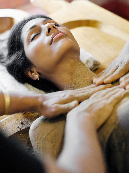 Woman Receiving Udwarthanam, Ayurvedic Powder Massage, Kairali Ayurvedic Health Resort, Palakkad, Kerala, India. In Udwarthanam, powder is rubbed on the front and back of body by a therapist, using a two- handed in a motion towards the client's heart. No oil is used in this treatment. Udwarthanam helps balance the kapha dosha, and aids in correcting metabolism and eliminating excess fat from the body.