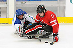 Adam Dixon (11) of Team Canada keeps the puck away from an Italian defender during a sledge hockey game at UBC Thunderbird Arena in Vancouver. Credit:CPC/HC/Matthew Manor.