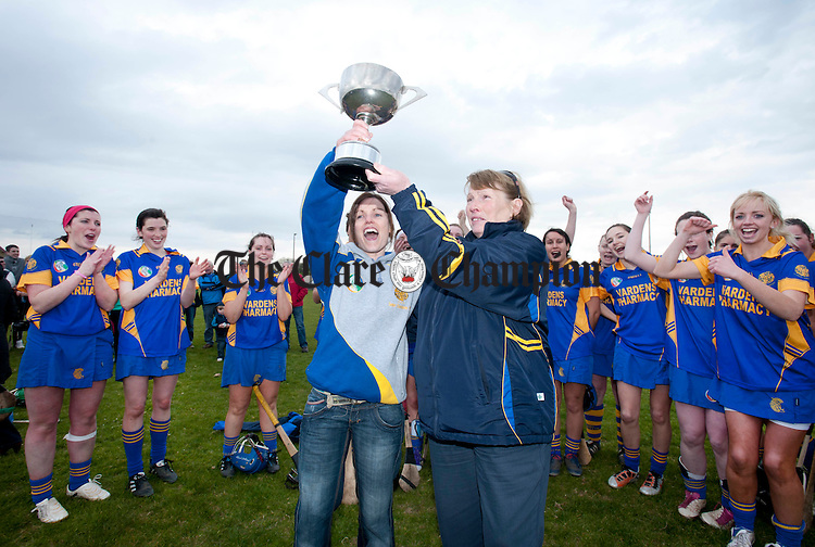 Bridie O' Looney from the Clare Camogie Board presents Erica Minogue, Newmarket captain, with the trophy. Photograph by Declan Monaghan