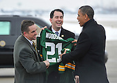 United States President Barack Obama (R) is given a signed Green Bay Packers Charles Woodson jersey by Wisconsin Governor Scott Walker (C) and Green Bay mayor Jim Schmitt as he arrives at Austin Straubel International Airport in Green Bay, Wisconsin on Wednesday, January 26, 2011. President Obama, Vice President Joe Biden and other members of the President's Cabinet traveled across the country Wednesday to highlight the administration's efforts to rebuild the American economy.     .Credit: Brian Kersey / Pool via CNP
