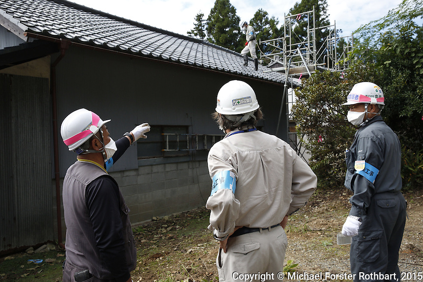 Ben Takeda, a Fukushima decontamination supervisor working for the Joint Venture in Tomioka, Japan, in the Fukushima Exclusion Zone, checks in with laborers working to decontaminate homes and commercial properties. Almost all developed properties in Tomioka are now getting cleaned or demolished four and a half years after the Fukushima Daiichi nuclear power plant disaster. Full caption to come.<br /> <br /> &copy; Michael Forster Rothbart Photography<br /> www.mfrphoto.com &bull; 607-267-4893<br /> 34 Spruce St, Oneonta, NY 13820<br /> 86 Three Mile Pond Rd, Vassalboro, ME 04989<br /> info@mfrphoto.com<br /> Photo by: Michael Forster Rothbart<br /> Date:  10/6/2015<br /> File#:  Canon &mdash; Canon EOS 5D Mark III digital camera frame B20522