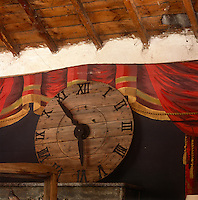 A wooden clock face wtih painted roman numerals hanging on a wall painted with a trompe l'oeil image of curtaans.