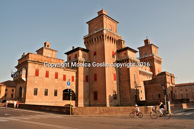 A mother and daughter on bikes, ride past the Castle Estense, a medieval castle with a moat around it in the center of town
