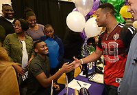 NWA Democrat-Gazette/ANDY SHUPE<br /> Fayetteville quarterback Darius Bowers (left) is congratulated Wednesday, Feb. 6, 2019, by friend Radarian Cobbs after Bowers signed to play football with the University of Central Arkansas during a signing ceremony at Fayetteville High School.