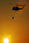 A Bell UH-1 helicopter, operatied by Lundsford Air Consulting Inc., fliles across the setting sun with a firefighting bucket slung beneath, at the Flagler County Airport, Monday, Oct. 15, 2004.  The helicopter was on a training flight to instruct pilots and crewmembers, of the Air Force of the Dominican Republic, in the use of airborne firefighting equipment.(Brian Myrick)