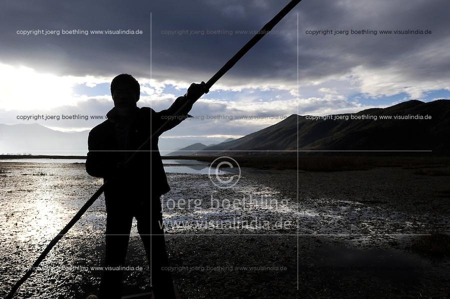 CHINA Yunnan, oarsman at Lugu Lake / CHINA Provinz Yunnan , Lugu See, Mosuo Mann mit Boot, Mosuo ist eine ethnische Minderheit