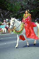 woman wearing flower leis and a traditional wrapped skirt, or pa'u, rides on horseback in the Aloha Festivals Parade