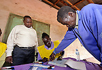 As Roman Catholic Father Thomas Bagbiowia (left) observes, Margaret David Solomon, a poll worker in Nzara, in Southern Sudan's Western Equatoria State, helps a man put his fingerprint on a registration document on the first day of a 17-day registration period in preparation for January's referendum on secession from the country's north. Bagbiowia, the parish priest in nearby Riimenze, is a member of the local election commission and led a team that trained poll workers. Voters are expected to choose overwhelmingly for independence. NOTE: In July 2011 Southern Sudan became the independent country of South Sudan.