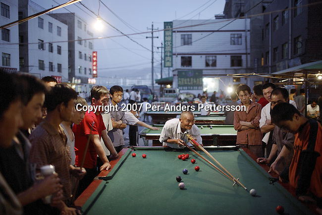 LANZHOU, CHINA - JUNE 5: Construction workers play pool in the evening near their living quarters on June 5, 2007 in central Lanzhou, China. They work on the many high-rise buildings that are being constructed here. Thousands of workers come from rural areas to China's cities to work in the booming economy. (Photo by Per-Anders Pettersson).
