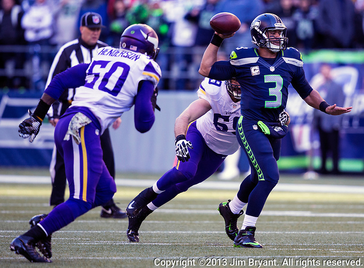 Seattle Seahawks quarterback Russell Wilson passes under pressure against the  Minnesota Vikings at CenturyLink Field in Seattle, Washington on  November 17, 2013. Wilson ran for 54 yards and passed for  two touchdowns in Seahawks 41-20 win over the Vikings.  ©2013.  Jim Bryant. All Rights Reserved.