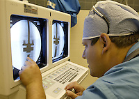 Dr. Joel Mayerson analyses the before and after x-rays of Derick Byrd's leg to make sure the proper length was added to Derick's prosthesis during surgery at Children's Hospital, Friday June 17, 2005, in Columbus, Ohio. Derick's surgery was a non-invasive procedure using an electromagnetic field to create heat that softens a polymer, allowing Derick's plastic and titanium prosthesis to expand.<br />