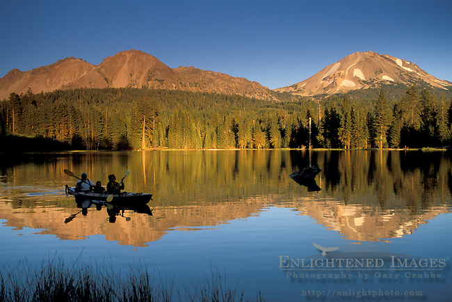 Sunset light on mountain over Family paddle kayak on blue water at Manzanita Lake, Lassen Volcanic National Park, California