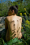 Shadows of flowering plants on young womans bare back
