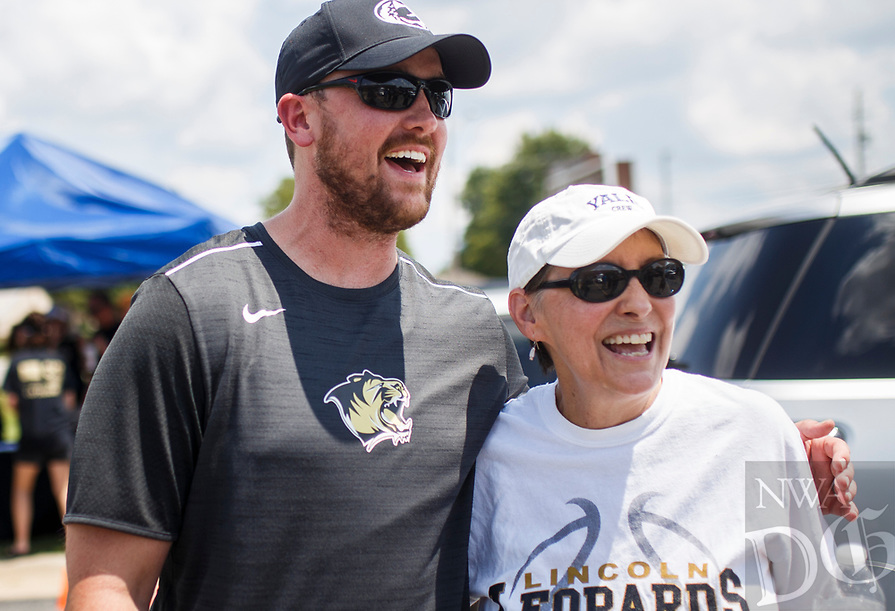 NWA Democrat-Gazette/CHARLIE KAIJO Lincoln Jr. High School special education teachers David Bradley and Denise Fedon (from left) laugh, Sunday, August 5, 2018 at the parking lot of Sport Clips in Bentonville. <br /><br />David Bradley, a special education teacher at Lincoln Jr. High and volunteer football coach at Bentonville High School, was recently diagnosed with an aggressive brain cancer. This is a fundraiser for him and includes Lincoln Jr. High and BHS football, baseball and basketball players and cheerleaders washing cars, RonÕs Burgers selling food, Kona Ice selling snow cones and Sport Clips donating $10 for every MVP haircut.<br /><br />The car wash was only through Sunday, but Sports Clips hopes to raise $10,000 by August 11 through the donations.