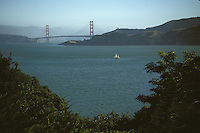 Sailboat sailing in the bay with the Golden Gate Bridge in the distance, San Francisco, California