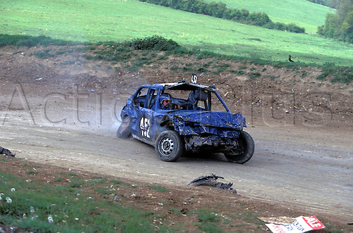 Banger cars race round the dirt circuit, BANGER RACING action, Layhams Farm, New Addington, Surrey, 9405. Photo: Richard Francis/Action Plus...motorsport car motor stock cars dirt oval racing wreck