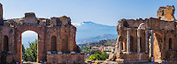Panoramic photo of Taormina Greek Theatre aka Teatro Greco, ruins of columns at the amphitheatre, with Mount Etna Volcano in the background, Sicily, Italy, Europe. This is a panoramic photo of Taormina Greek Theatre aka Teatro Greco, showing ruins of columns at the amphitheatre, with Mount Etna Volcano in the background, Sicily, Italy, Europe