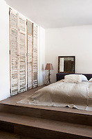 Old shutters have been restored and used as wardrobe doors in this minimal bedroom