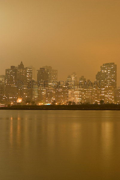 Skyline of Manhattan's Upper East Side Illuminated on an Overcast Night, The East River and the southern edge of Roosevelt Island in the foreground