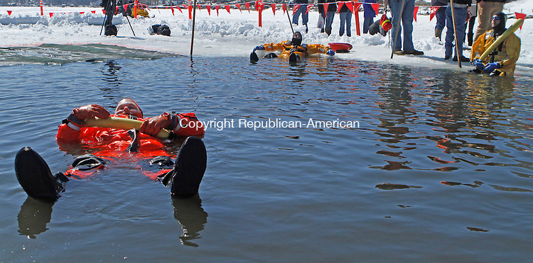 Winsted, CT-030913MK15  Memebers of the Winsted fire rescue squad relax in the thirty-two degree water in Highland Lake just before the annual Penguin Plunge on Saturday afternoon in Winsted. Sharon Pelkey, director of development northwest region, said that there were one-hundred forty-eight jumpers and the event raised over $54,500 for the Special Olympics. Michael Kabelka Republican American