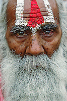 Colorful old man with long beard at train station in Udaipur, India.
