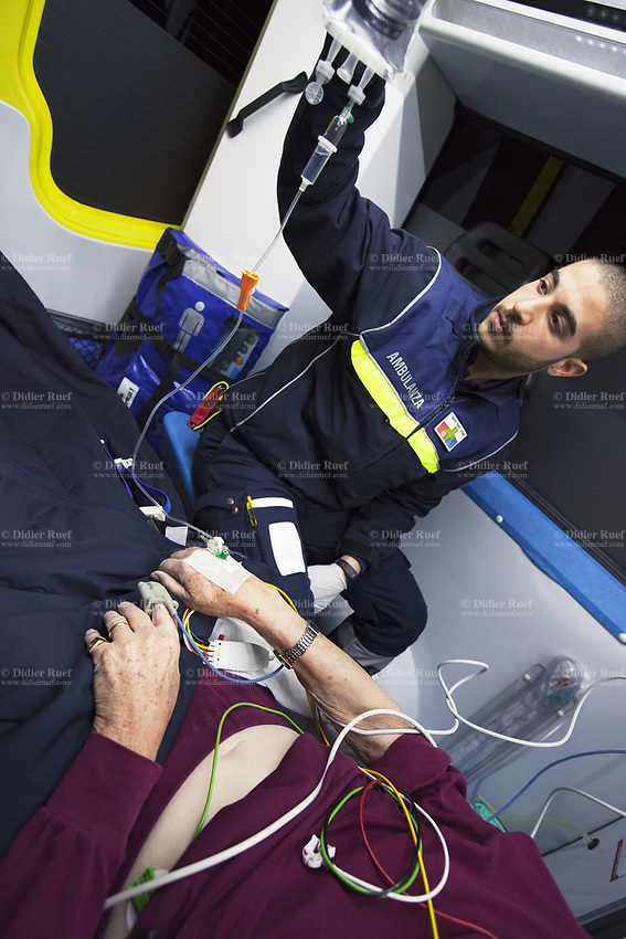 Switzerland. Canton Ticino. Pregassona. A senior man lying down on an emergency medical stretcher is brought to hospital for medical examination. The elderly man is suffering from a heart problem. The paramedic, wearing a blue uniform and medical gloves, is a volunteer specifically trained in emergency rescue. He checks the patient's intravenous infusion of saline solution. The patient is also connected to a monitor which controls a set of vital functions, such as  electrocardiogram, blood pressure's measurement, respiratory rate and pulse oximetry (oxygen saturation). The Croce Verde Lugano is a private organization which ensure health safety by addressing different emergencies services and rescue services. The Croce Verde Lugano is a private organization which ensure health safety by addressing different emergencies services and rescue services. Volunteering is generally considered an altruistic activity where an individual provides services for no financial or social gain to benefit another person, group or organization. Volunteering is also renowned for skill development and is often intended to promote goodness or to improve human quality of life. Medical gloves are disposable gloves used during medical examinations and procedures to help prevent cross-contamination between caregivers and patients. Medical gloves are made of different polymers including latex, nitrile rubber, polyvinyl chloride and neoprene. Pregassona is a quarter of the city of Lugano. 20.01.2018 © 2018 Didier Ruef