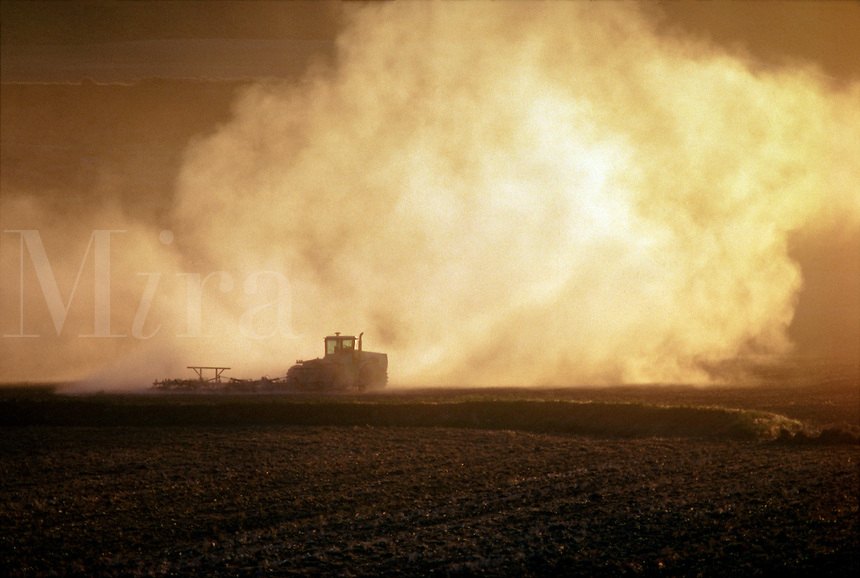Cloud of dust behind a tractor in a field #5341A. Idaho.