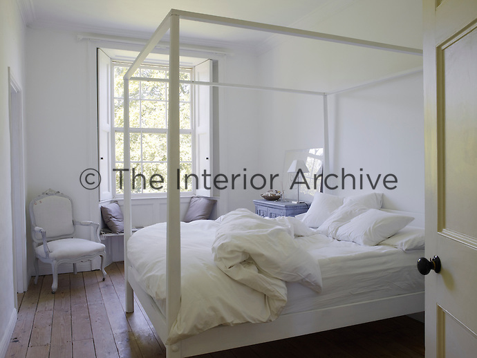 In this tranquil white-painted bedroom a hint of colour comes from an antique grey-painted cupboard next to the four-poster bed and some cushions on the window seat