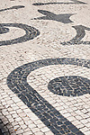 A sidewalk in Porto, Portugal with white and black stones in swirling patterns.