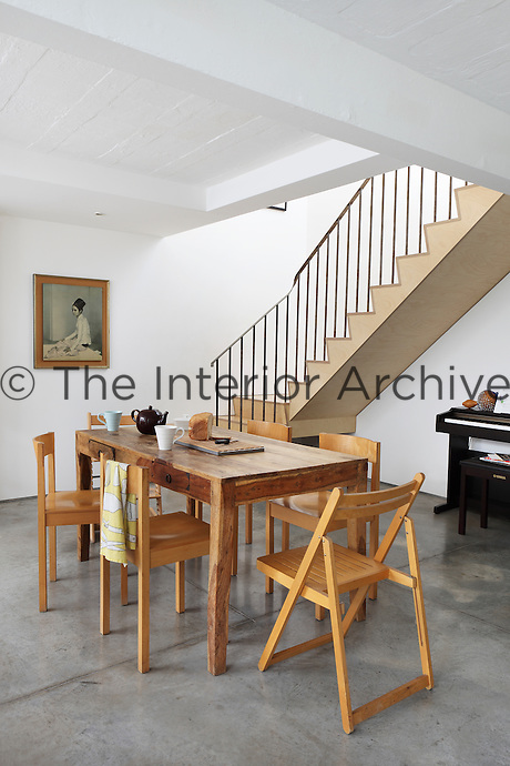 The dining area occupies a place in the open plan scheme close to the simple staircase leading to the first floor