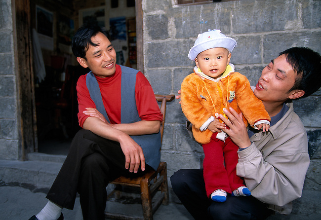 Proud father holding baby boy on lap; rural village of Xaio He; afternoon; near Wuxi, China, Asia; 042503