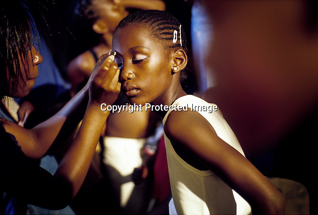 A girl gets a makeup backstage before a beauty competition on December 20, 2004 in Soweto, Johannesburg, South Africa. Soweto, the biggest township in South Africa, has a population of about 3.5 million. A growing number of people belong to a new black middle-class and elite in the country, and they have money to spend on beauty, and clothes. Many have risen from poverty in the townships to a different lifestyle, since the fall of Apartheid and the start of democracy in the country in 1994. (Photo by: Per-Anders Pettersson)