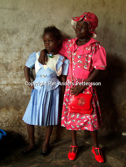 dicocon00162.Congo. Kinshasa. Children, girls Bebeto Lumueno, age 9, (left) and Chancy Mbungu, age 10 has dressed up and is ready to go to a church service on February 28, 2002 in Ngafani, a village about 20 kilometers outside Kinshasa, Congo. Bebetu is in primary school and wants to be a sewing lady when she grows up. This poor village outside Kinshasa is located close to the Congo River..©Per-Anders Pettersson/iAfrika Photos