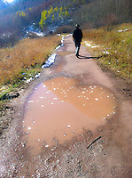 Love. Heart made of mud on country path, with person man walking ahead, in winter with snow. Amazing unexpected romantic love in puddle, divine intervention. Love the earth