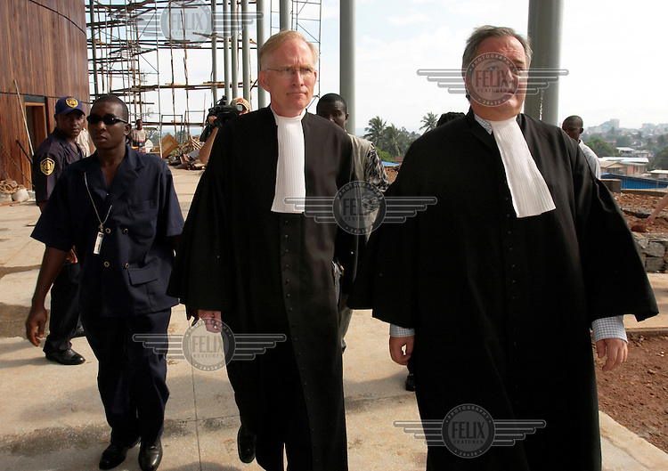 The first day of proceedings at the Special Court for Sierra Leone, which was set up jointly by the government and the United Nations to investigate war crimes. David Crane (centre), chief prosecutor, enters the court flanked by a member of his prosecution team (right) and a security official (left).