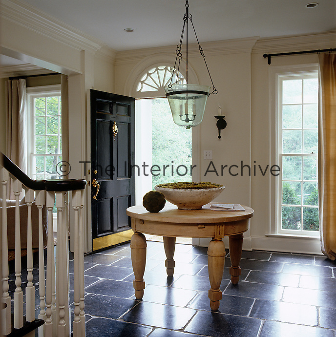 The juxtaposition of an oversize honey-coloured antique table and pale walls against dark bluestone floors in the entrance hall has a quiet power