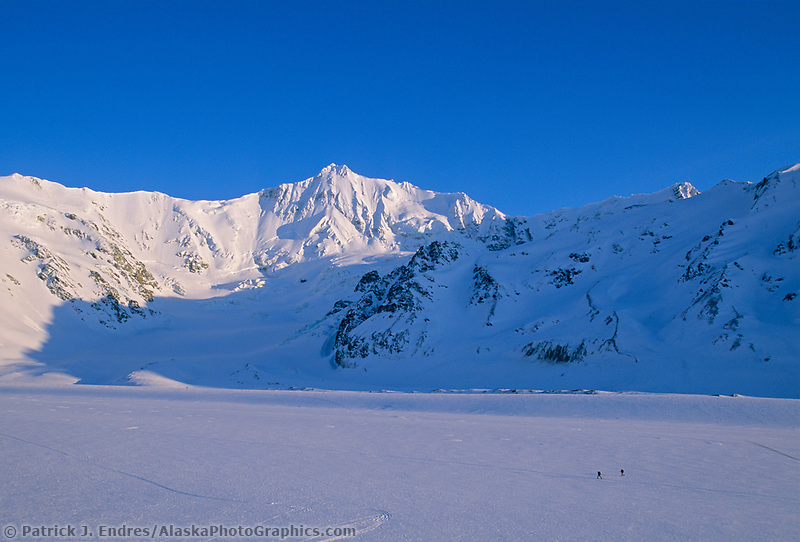 Mountaineers ski across the Canwell Glacier, mt institute in the distance, Alaska Range.