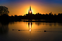 02/11/18<br /> <br /> Ahead of a cold night the setting sun shines through the central spire of Lichfield Cathedral, and is reflected in Stowe Pool.<br /> <br /> The Staffordshire medieval cathedral  is the only English cathedral with three spires. The three spires are often referred to as 'the Ladies of the Vale'.